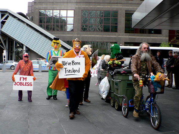 Joey Skaggs Pedals his Mobile Homeless Home Accompanied by Band of Pissed-off Muppets to Goldman Sachs Office in New York, 2012