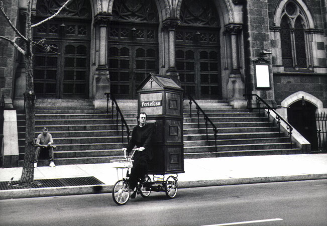 Father Anthony Joseph, aka Joey Skaggs, Pedals Portofess, his Mobile Confessional Booth, to Democratic Convention, 1992